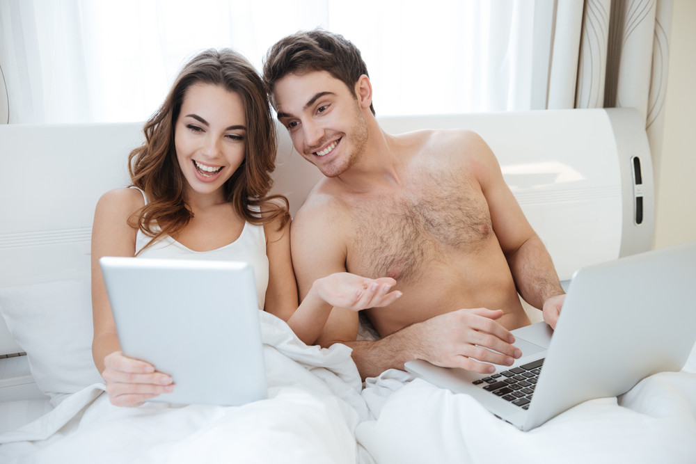Cheerful young couple with laptop and tablet talking in bed