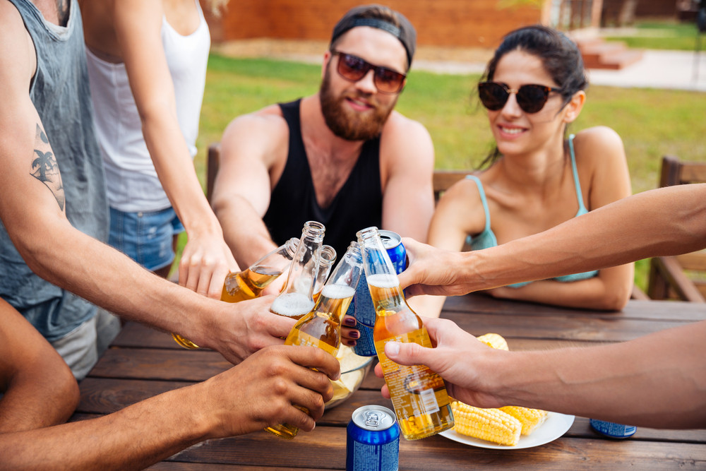 Cheerful young friends celebrating and drinking beer outdoors