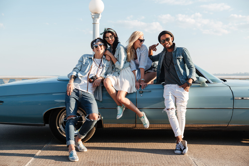 Cheerful young friends standing and smiling near the car