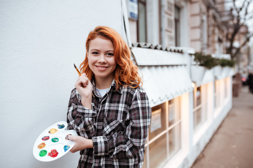 Cheerful young lady painter with red hair walking on the street. Look at camera while holding palette and paintbrush outdoors.
