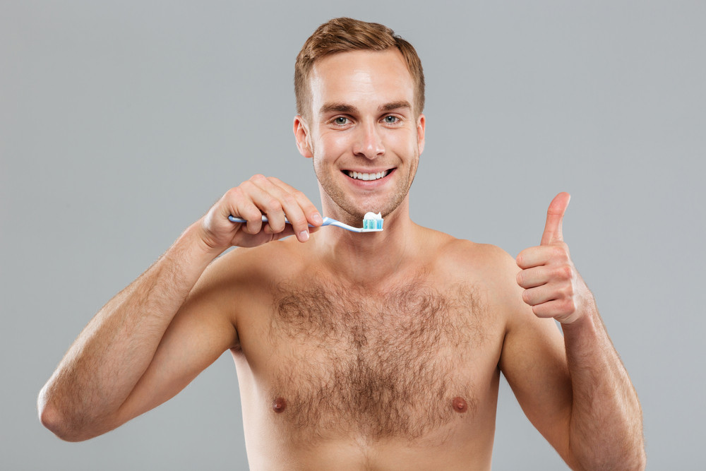 Cheerful young man holding toothbrush and showing thumbs up