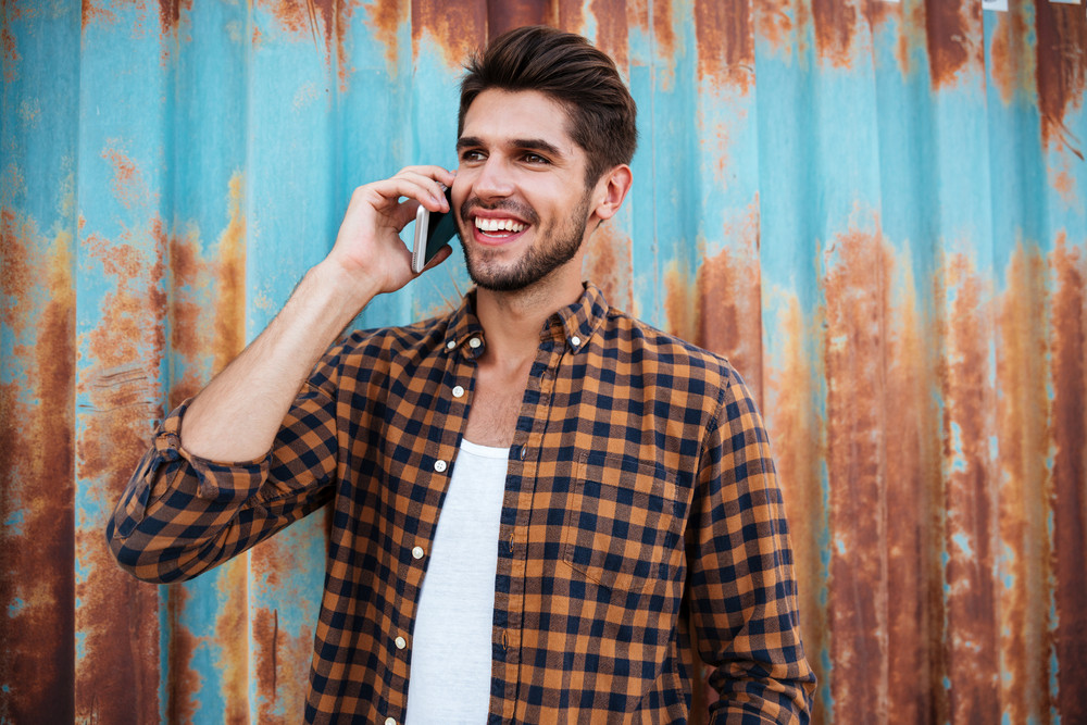 Cheerful young man in checkered shirt standing and talking on mobile phone
