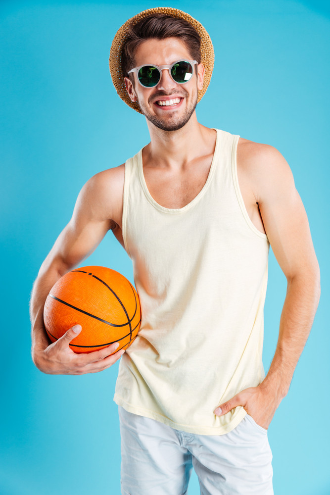 Cheerful young man in hat and sunglasses holding basketball ball