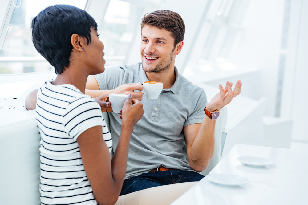 Cheerful young man sitting in cafe and drinking coffee with young african woman