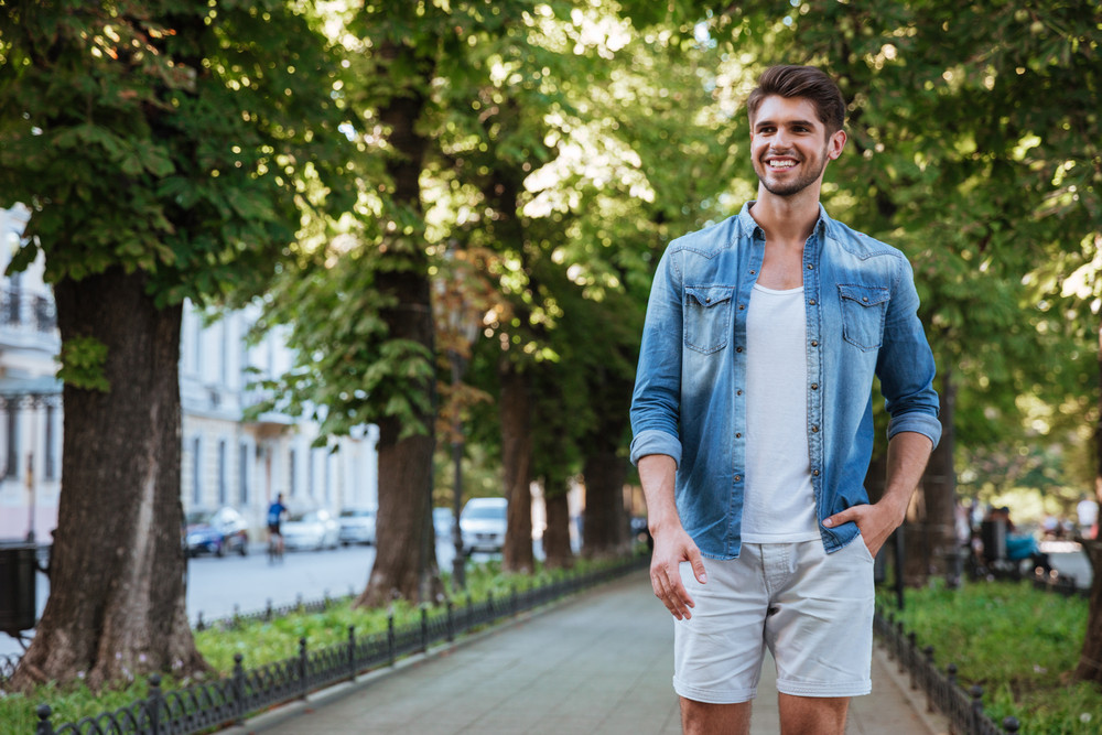 Cheerful young man walking in the city