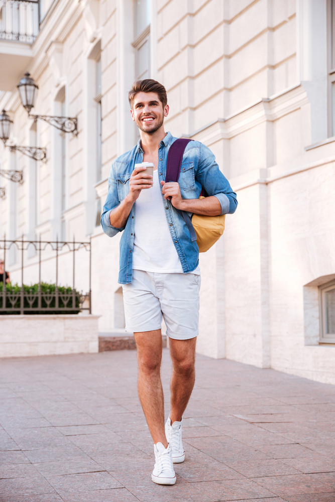 Cheerful young man with backpack walking and drinking coffee in the city