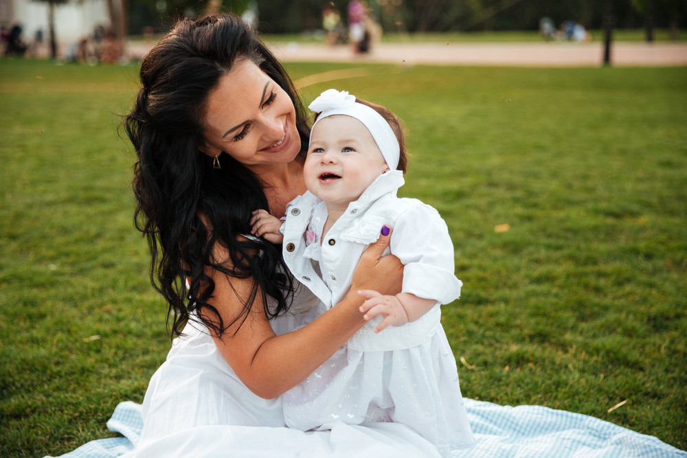 Cheerful young mother sitting with her little daughter outdoors