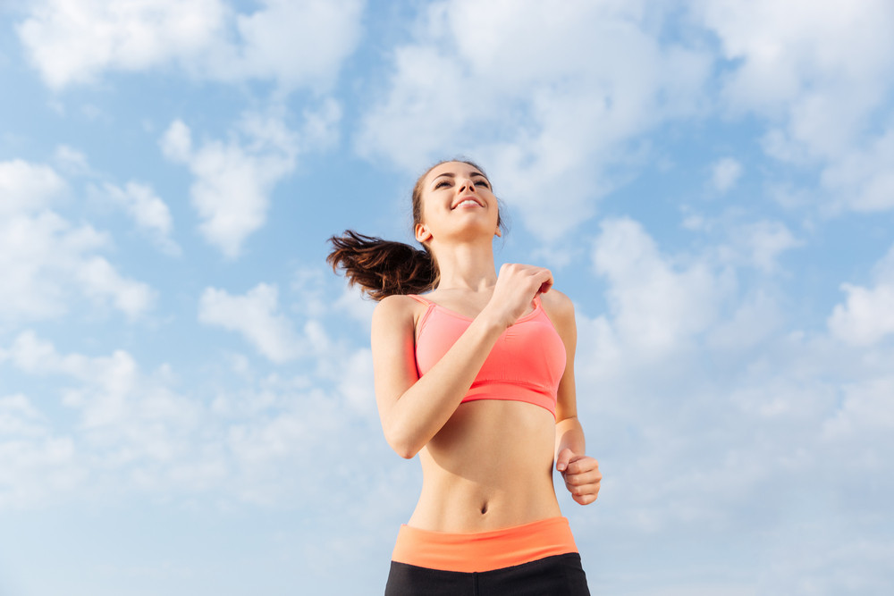Cheerful young sportswoman running outdoors in sunny day