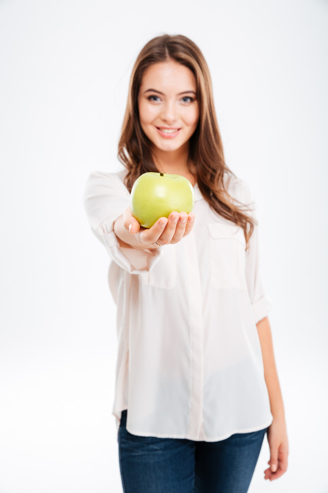 Cheerful young woman giving apple at camera isolated on a white background. Focus on apple