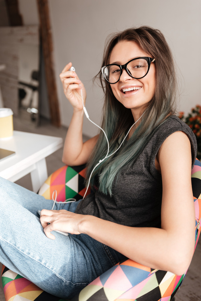 Cheerful young woman in glasses listening to music from cell phone at home