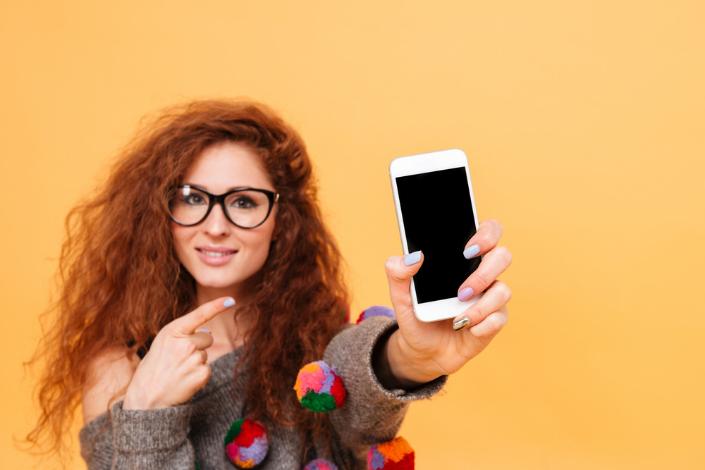 Cheerful young woman with red hair holding mobile phone and pointing it isolated on orange