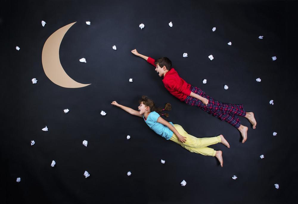 Children getting ready for bedtime. Studio shot on a black background.