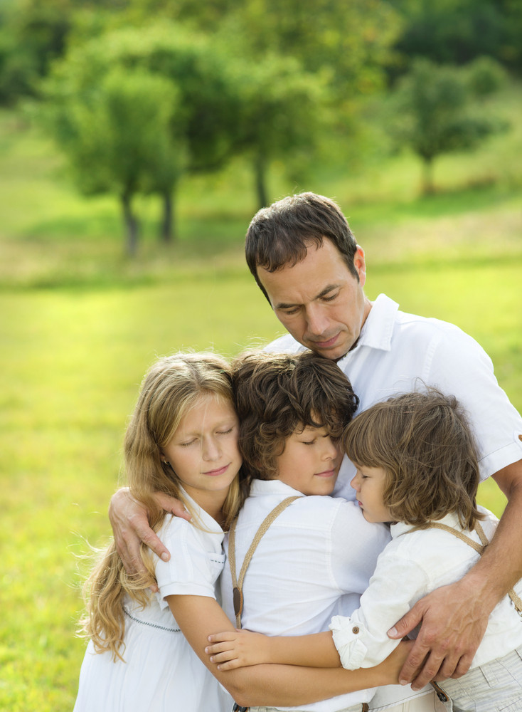Children giving hugs to their dad on the meadow.
