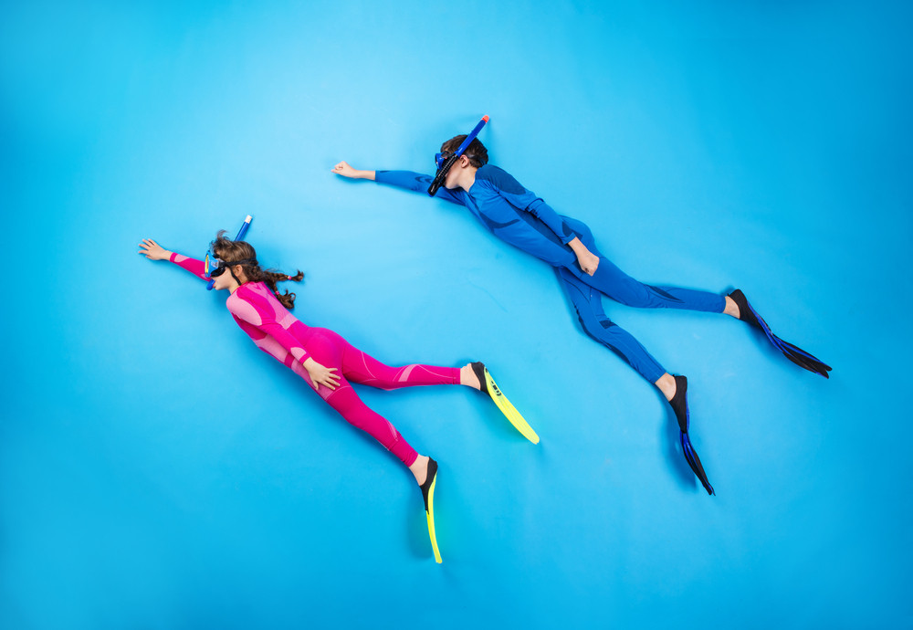 Children scuba diving deep in the sea. Studio shot on a blue background.