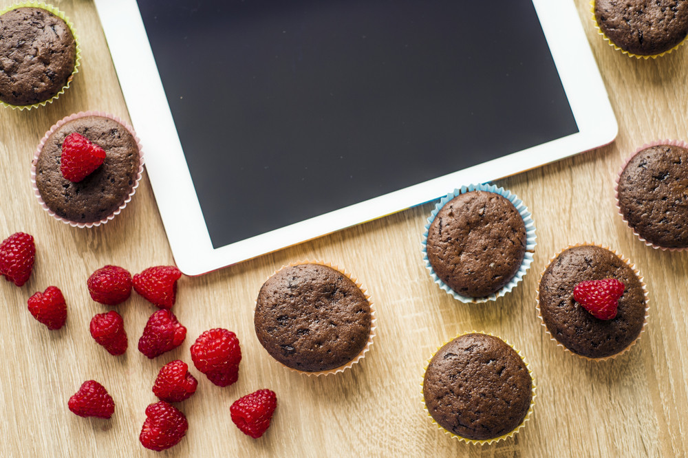 Chocolate muffins with fresh raspberries and digital tablet on the table