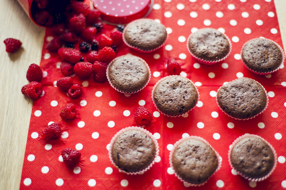 Chocolate muffins with fresh raspberries on the table