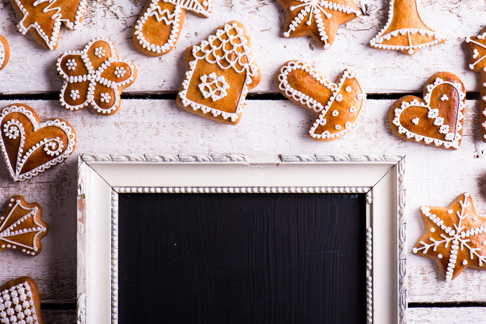 Christmas composition with gingerbreads and picture frame. Studio shot on white wooden background.