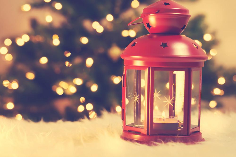 Christmas lantern on white carpet with tree at night