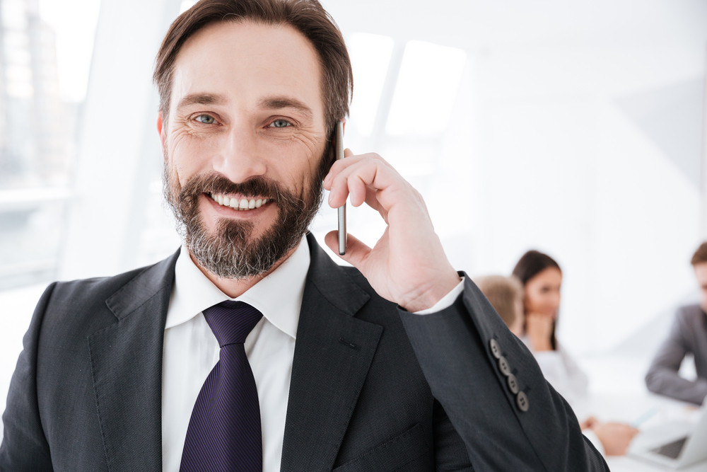 Close up Bearded Business man talking at phone in office with colleagues on background