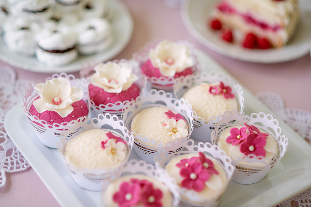 Close up, cupcakes on tray decorated with pink flowers laid on table with pink tablecloth and handmade lace. Candy bar.