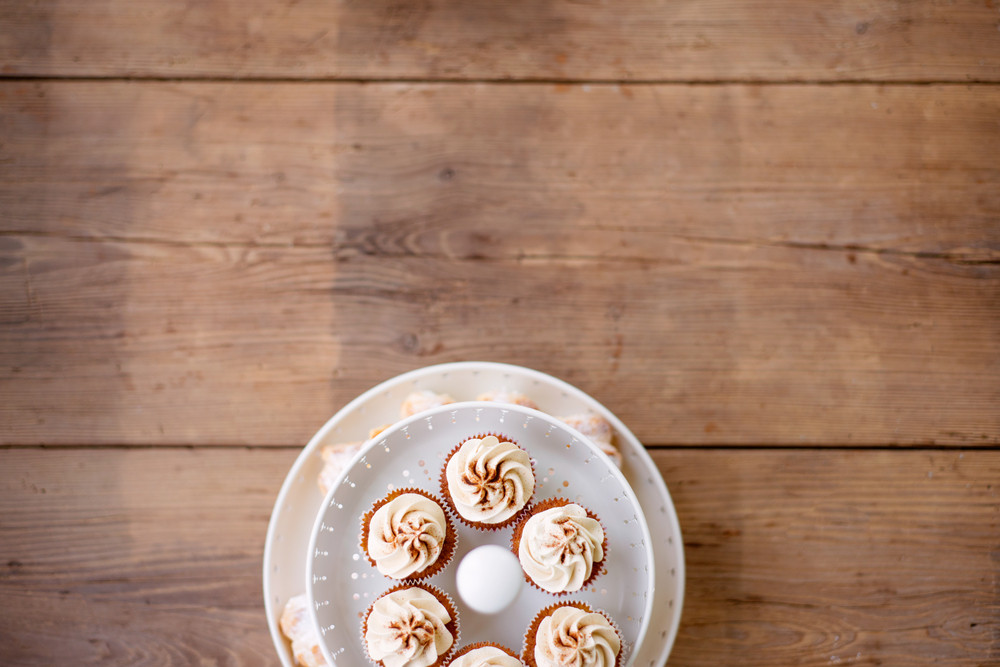 Close up, cupcakes with vanilla cream in white cakestand. Copy space. Studio shot on brown wooden background.