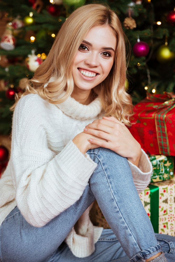 close up girl in sweater sitting on the floor near the fir tree and