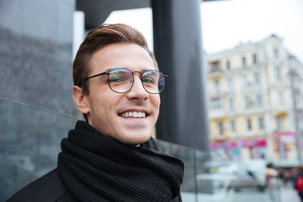 Close up happy business man in glasses looking at camera on the street
