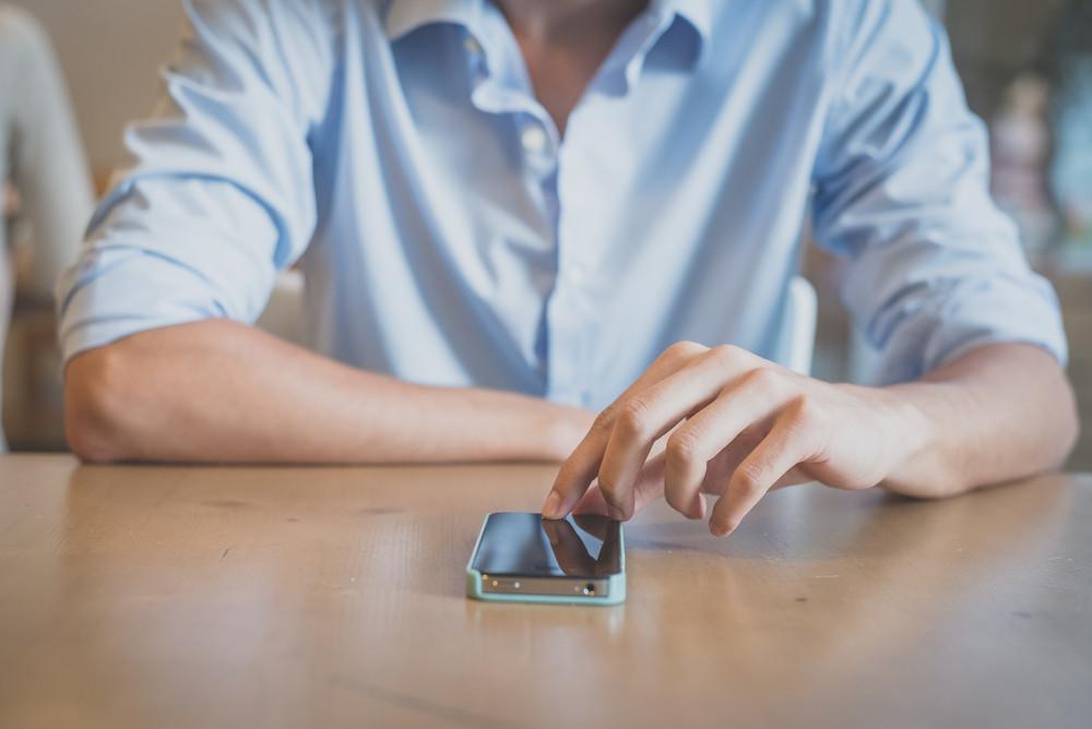 close up man hand using smartphone at the bar