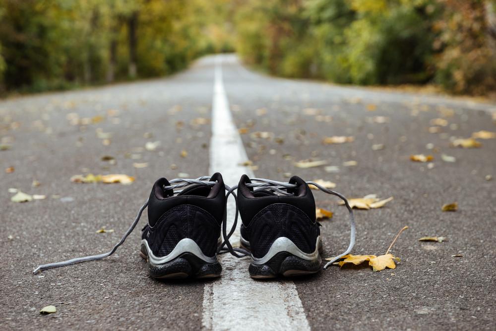 Close up new black running shoes on asphalt road. on road markings