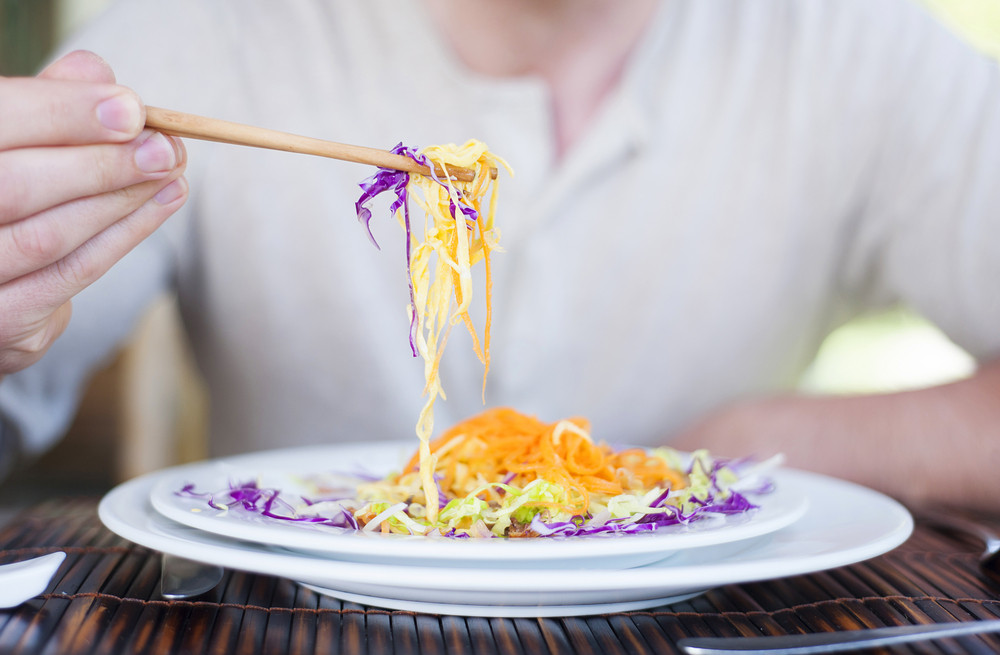 Close up of a man enjoying a meal with chopsticks in vietnamese restaurant