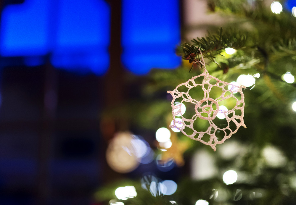 Close up of a white crocheted decoration hang on Christmas tree