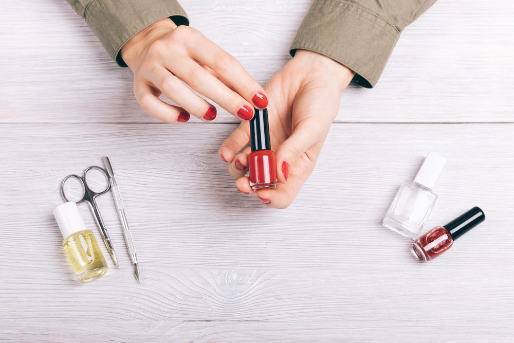 Close-up of a woman holding a manicure red lacquer in hands, top view