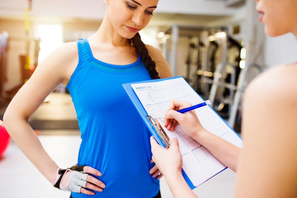 Close up of an attractive fit woman in blue singlet in a gym with her personal trainer writing into exercise plan on clipboard