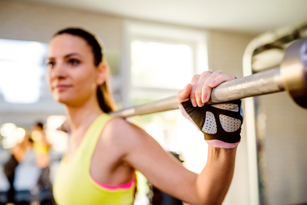 Close up of attractive fit woman in gym exercising with weights
