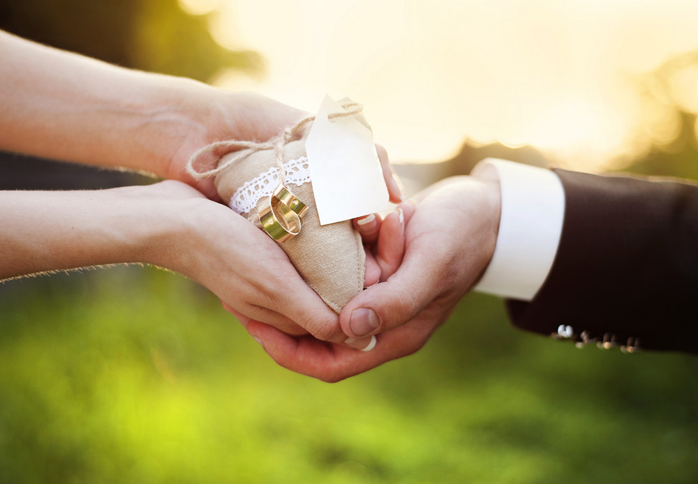 Close up of bride and groom's hands holding decorative heart in their hands in green nature