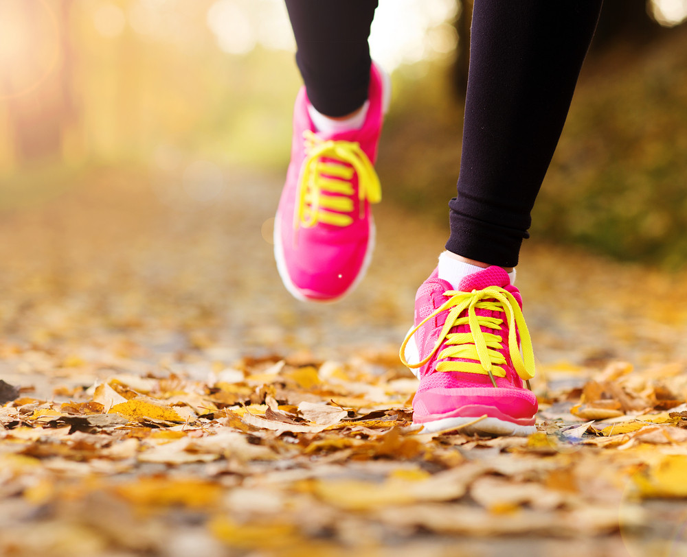 Close up of feet of a runner running in autumn leaves training exercise