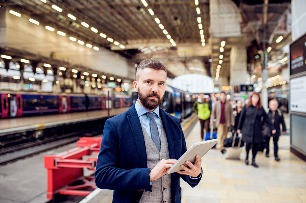 Close up of hipster businessman waiting at the train station platform holding a tablet