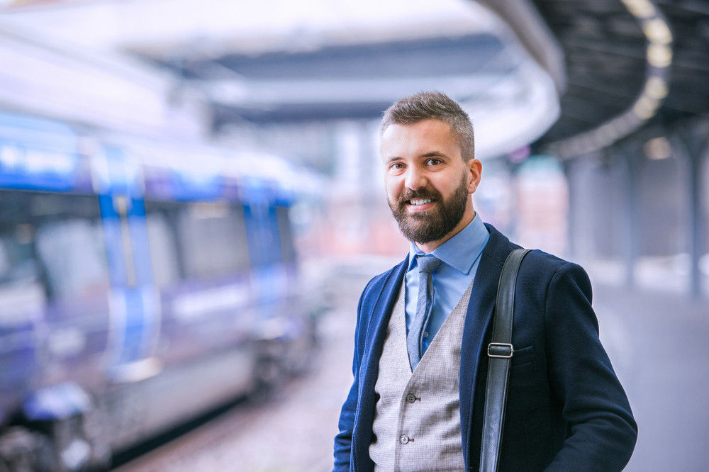 Close up of hipster businessman waiting at the train station platform