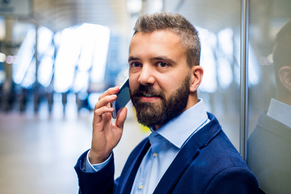 Close up of hipster businessman with smartphone standing on subway station