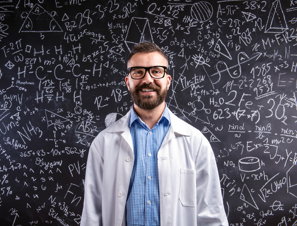 Close up of hipster teacher in white coat and eyeglasses against big blackboard with mathematical symbols and formulas. Studio shot on black background.