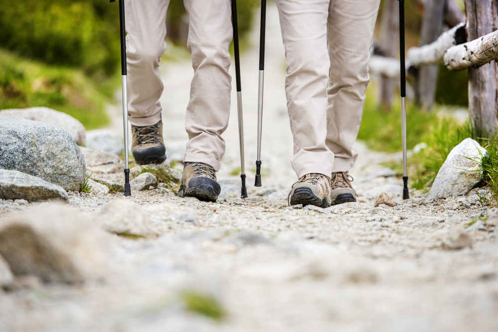 Close-up of legs of senior couple hiking at the beautiful mountains