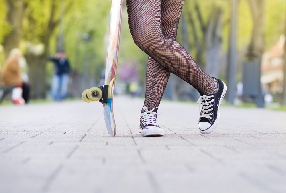 Close-up of legs of teenage girl holding skateboard