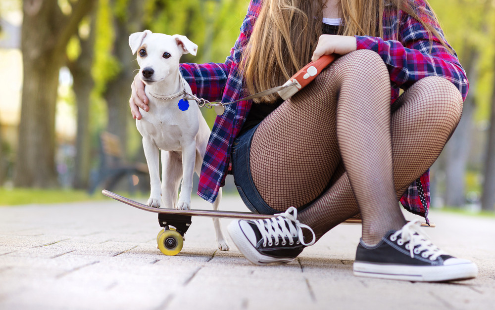 Close-up of legs of teenage girl on skateboard with her dog