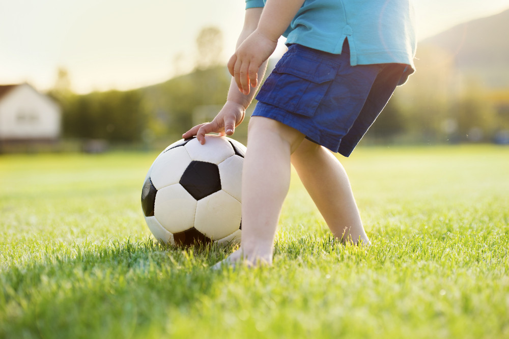 Close-up of little boy playing football on football pitch