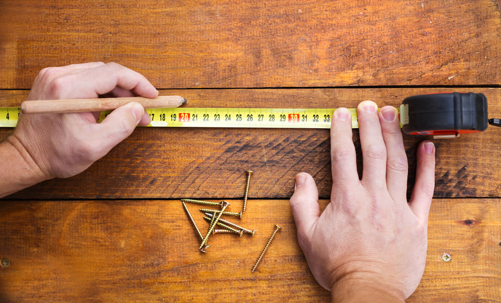Close up of male hand measuring and marking wood flooring with tape measure