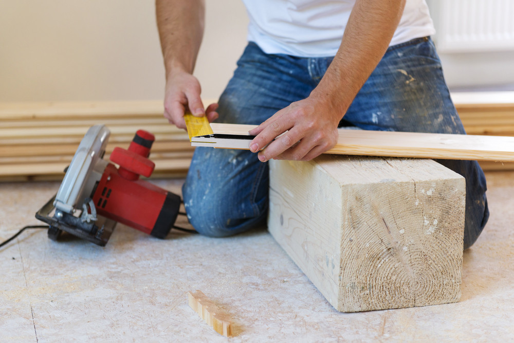 Close up of male hands measuring wood flooring