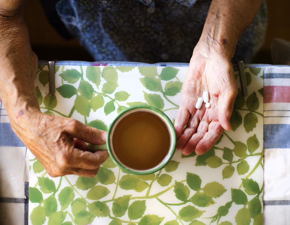 Close up of old woman's hands holding pills in kitchen kitchen