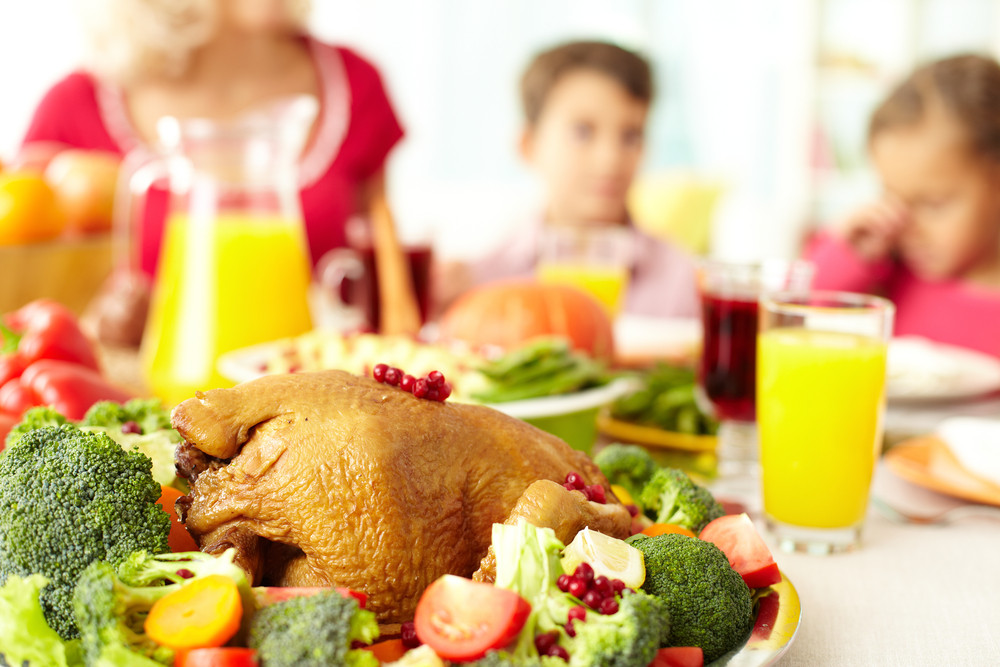 Close-up of roasted turley served with broccoli on background of siblings and woman