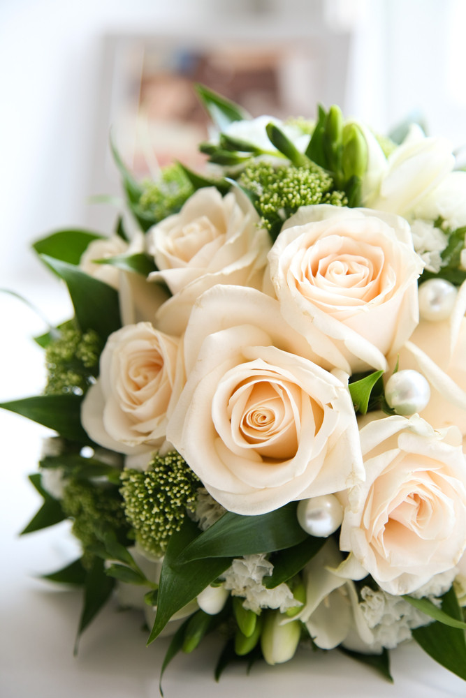 Close-up of rose bouquet decorated with pearls and other decorative flowers and plants