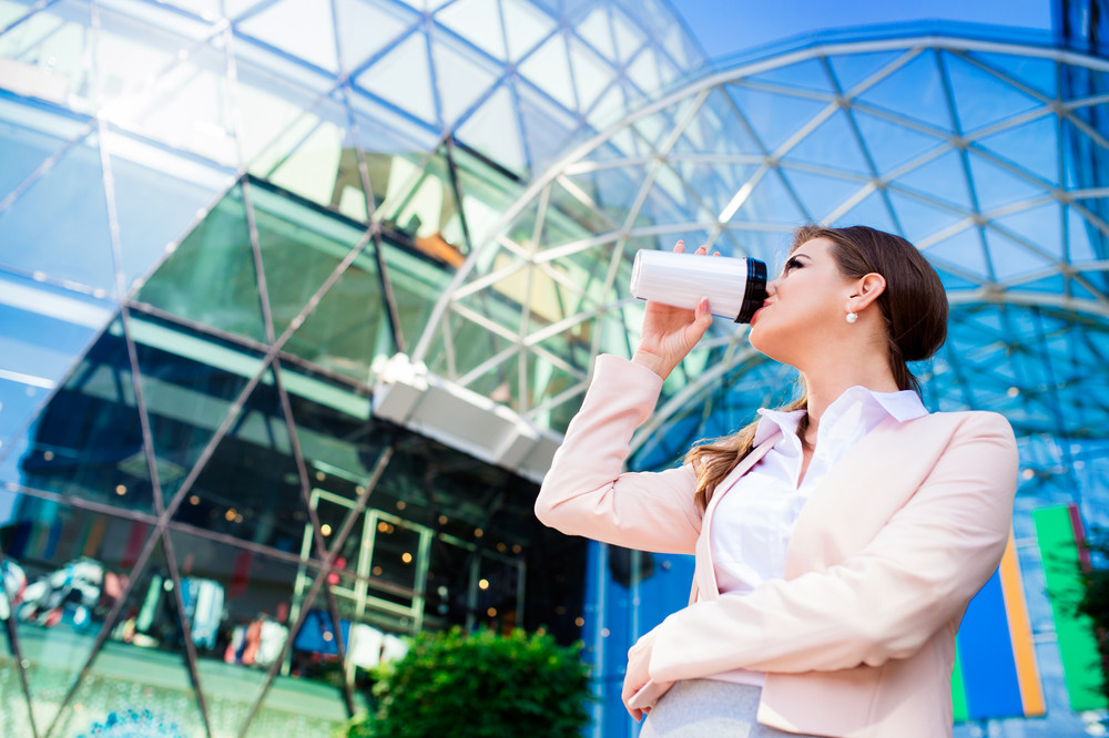Close up of smiling elegant businesswoman drinking from thermo coffee cup in pink jacket and white shirt against glassy modern office building